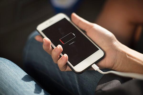 Imagen de cabecera para cuánto cuesta cargar un móvil con una mujer sujetando un iPhone blanco mientras carga