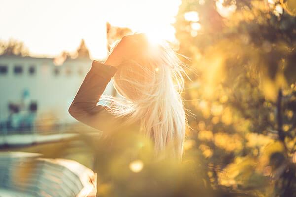 Mujer secándose el pelo al Sol