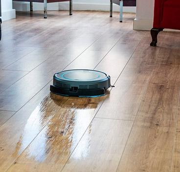 Robot friegasuelos Cecotec Conga Wet fregando un suelo de madera dejando un rastro de agua