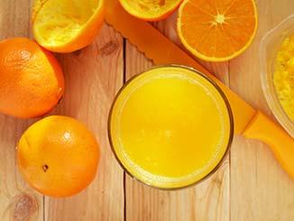 Naranjas cortadas junto a un vaso lleno de zumo