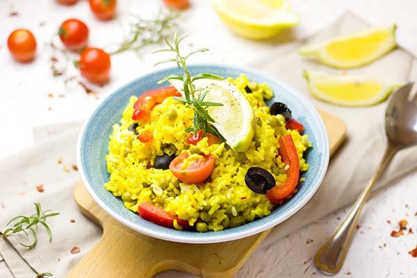 Paella en un plato con tomates y un huevo cocindo