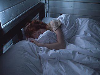 Mujer durmiendo en una cama con sábanas blancas
