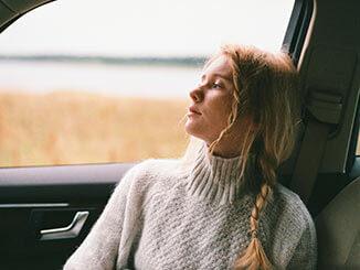 Mujer mirando a través de la ventana de un coche