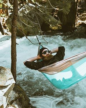Persona durmiendo en una hamaca junto a un rio